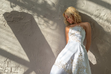 Bride stands about the plastered walls