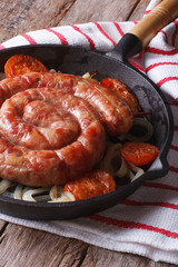 Grilled sausage with onions in a pan close-up. Vertical