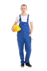 young handsome man builder in blue uniform holding helmet isolat