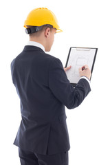 young handsome business man in yellow builder's helmet writing s