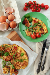 Omelet with tomatoes and fresh rucola leafs for breakfast