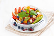 delicious fruit and berry salad in white bowl