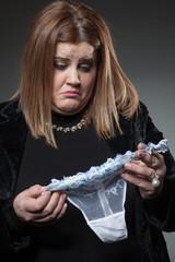 Sad woman holding thong