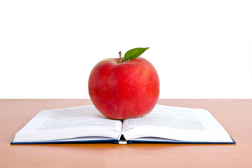 a opened student book with red apple