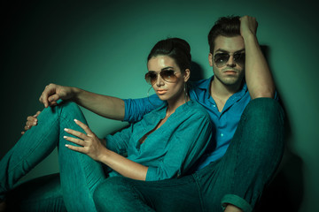 fashion couple sitting on studio background