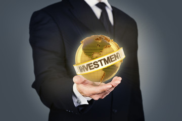 Businessman holding a golden globe with investment text
