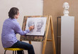 A man draws a pencil sitting at his easel.