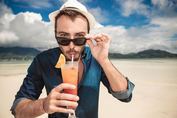 lman on the beach drinking a orange cocktail