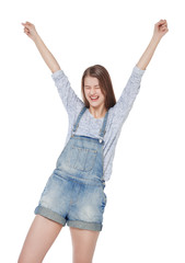 Happy young fashion girl in jeans overalls with hands up isolate