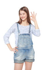 Happy young fashion girl in jeans overalls gesturing okay isolat