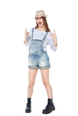 Young fashion girl in jeans overalls with horn gesture isolated