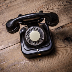 Old black phone with dust and scratches on wooden floor