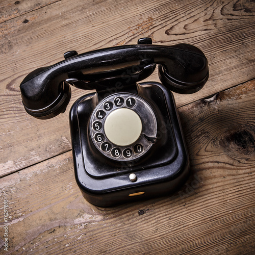 Papiers peints Retro Old black phone with dust and scratches on wooden floor