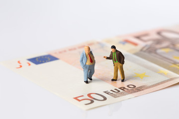 businessmen figurines standing on euro banknotes, financial deal