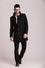 Handsome young business man wearing a long black coat