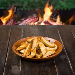 French Fries on Wooden table with Flaming BBQ Background