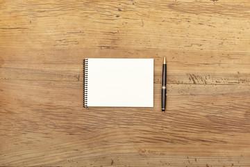 Notizblock und Kugelschreiber auf Holz
