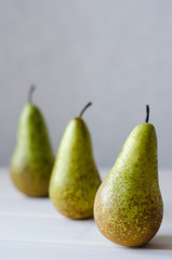 three green pear in a row on wooden white table
