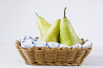 three green pears in a basket on wooden white table