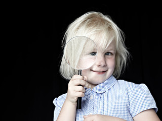 Blond girl laughing with magnifier