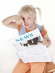 Cute blond child is reading newspaper