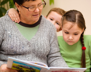 Grandmother is reading book with her grandchildren