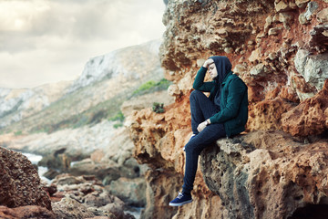 portrait of a young sad man sitting on the rocks.
