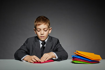 Boy in suit making paper planes