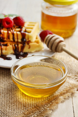 Bowl of honey on wooden table.