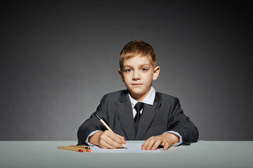 Boy in suit writing