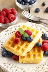 Waffles with syrup raspberries and blueberries