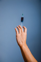 human hand holding a syringe with drug on gray background