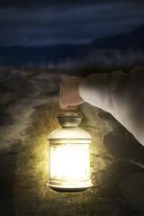 Right hand holding light illuminating dark road at night