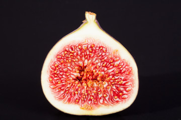 single sectioned fresh fig on black background