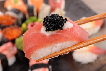 Tuna sushi with caviar held by chopsticks