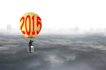 Businessman take 2015 bulb-shaped hot air balloon with cityscape