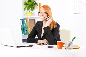 Young and pretty businesswoman in her office working