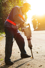 worker with pneumatic hammer drill equipment ready to breaking