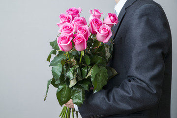 Man in suit with bouquet of pink roses