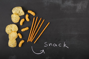 Snacks on dark chalkboard with copy-space