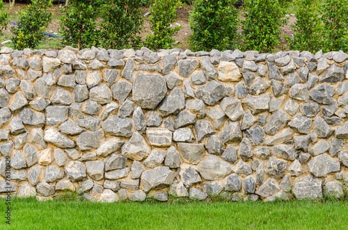 Foto op Plexiglas Wand fence real stone wall surface with cement on green grass field