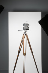 a movie camera on a tripod isolated on white