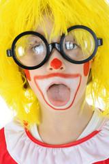 Clown mit Brille streckt Zunge raus