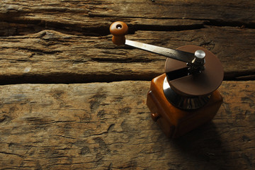 Nostalgic coffee grinder on old table and textured wood backgrou