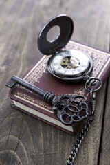 pocket watch and old key on  wooden table