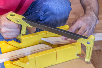 Using hand saw and miter box