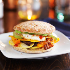 breakfast sandwich with egg, bacon, avocado and vegetables