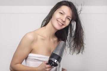 Attraktive Frau föhnt ihre Haare im Badezimmer