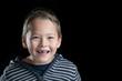 Kind mit Zahnlücke freigestellt vor schwarzem Hintergrund