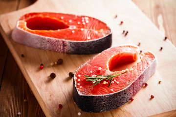 Raw salmon steak on wooden cutting board